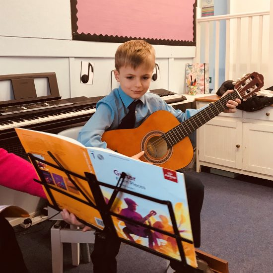Pupil learning guitar
