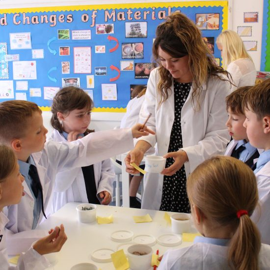 Teacher helping pupils with STEM experiment